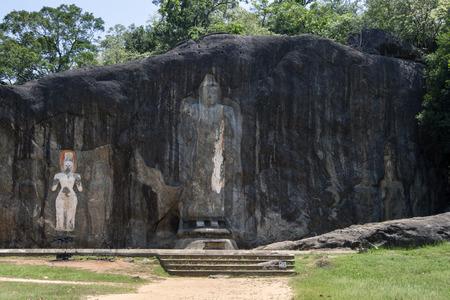 prin: La estatua de Buda 15 metros de alto es el protagonista de Buduruwagala, cerca Wellawaya en el centro de Sri Lanka. Que data del siglo 10, esta es la estatua de Buda de pie más alta en Sri Lanka. Las tres figuras a la izquierda de Buda se cree que son Prin Foto de archivo