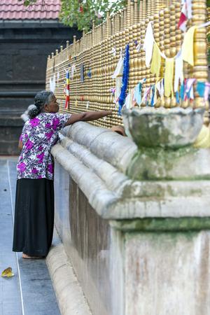 hindus: Una se�ora se coloca al lado del �rbol de la iluminaci�n sagrado en el templo de Kataragama en el sur de Sri Lanka. Kataragama es sagrado para los budistas, hind�es y musulmanes.