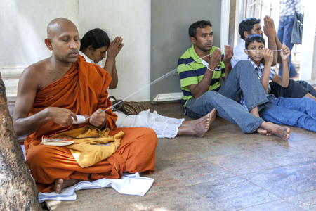 3rd century: A Buddhist monk dispenses string during a religious ceremony within the Mahavihara at Anuradhapura in Sri Lanka. The Mahavihara has relics dating back to the 3rd century BC. Editorial
