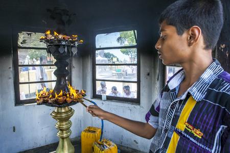 worshipping: A boy lights an oil cup at the Naga Pooshani Amman Kovil on Nainativu Island in the Jaffna region of northern Sri Lanka