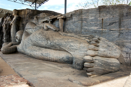 gal: The Gal Vihara at the ancient Sri Lankan capital of Polonnaruwa which includes a reclining Buddha statue, two seated Buddha statues and a standing Buddha statue all carved out of a single slab of granite rock. Polonnaruwa, Sri Lanka