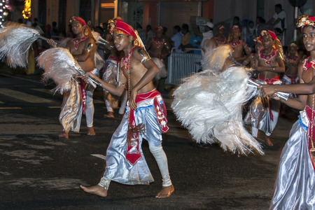 symbolically: Colourful Chamara Dancers perform a dance whereby the yak tails they hold symbolically fan the Sacred Tooth Relic during the Esala Perahara in Kandy, Sri Lanka. The Esala Perahera runs every year in late July or early August for ten days, ending on the Ni Editorial