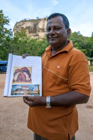 guia turistico: A Sri Lankan tour guide holds a drawing of what it is believed the Lions entrance to the summit of Sigiriya Rock looked like in the 5th Century AD.