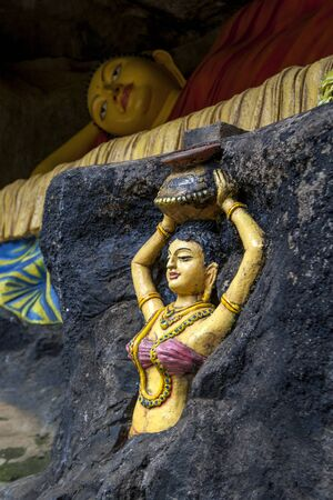 adams: A reclining Buddha with a female figure infront on the path up to Adams Peak in Sri Lanka.