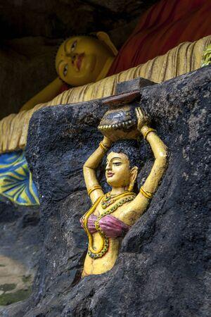 buddha sri lanka: A reclining Buddha with a female figure infront on the path up to Adams Peak in Sri Lanka.