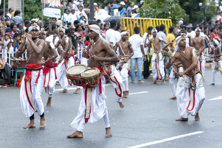 tapper: A Flute Player, Thammattam Player and Wood Tapper perform along the streets of Kandy during the day Perahera in Kandy in Sri Lanka. The Esala Perahera runs every year in late July or early August for ten days, ending on the Nikini poya full moon and is he