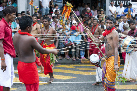 body piercing: A Kavadi Dancer with hooks piercing his body moves through the streets of Kandy during the day Perahera in Sri Lanka.Although the Kavadi Dancers are of Hindu faith, they are welcomed in the Buddhist Esala Perahera. The Esala Perahera runs every year in la