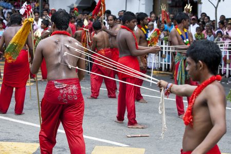 ye: A Kavadi Dancer with hooks pierced through his skin walks through the streets of Kandy during the day Perahera in Sri Lanka. Although the Kavadi Dancers are of Hindu faith, they are welcomed in the Buddhist Esala Perahera. The Esala Perahera runs every ye Editorial