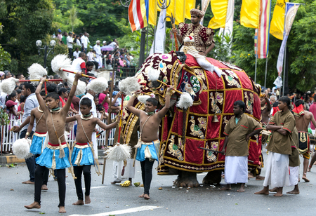 symbolically: Chamara Dancers perform ahead of a ceremonial elephant along the streets of Kandy during the day Perahera in Sri Lanka. Chamara Dancers perform a dance whereby the yak tails they hold symbolically fan the Sacred Tooth Relic. The Esala Perahera runs every  Editorial