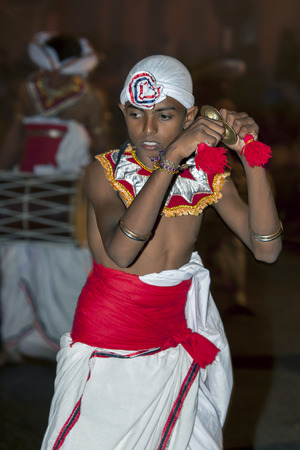 cymbal: A young Cymbal Player Thalampotakaruwo performs along the streets of Kandy during the Esala Perahera. The Esala Perahera festival runs every year in late July or early August for ten days, ending on the Nikini poya full moon and is held to honour the Sacr Editorial