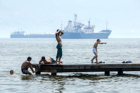 ocean liner: An ocean liner sails up the Bosphorus towards Istanbul as wrestlers play on a wharf at Izmit after being eliminated from competition at the Izmit Turkish Oil Wrestling Festival in Turkey. Editorial