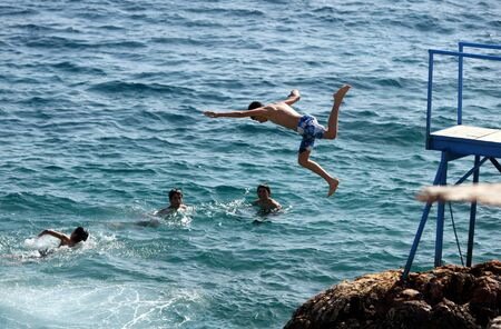 into: A boy cools off from the Turkish summer by diving off a jetty into the Mediterranean Sea at Kas in Turkey.