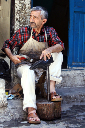 cobbler: A shoe cobbler repairs a shoe within the Urfa Bazaar.  Manly trades rarely seen in the western world still flourish in the many bazaars of eastern Turkey.