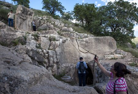 1st century: A lady takes a photo of the rock carving at Arsameia depicting King Antiochus shaking hands with Hercules. Arsameia was a kingdom built in the 1st century BC in eastern Turkey.