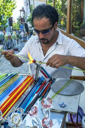 shaping: A glass blower starts the process of shaping an ornament is a street of Kalkan in Turkey. Kalkan is located on the Mediterranean Sea and is popular with British tourists.