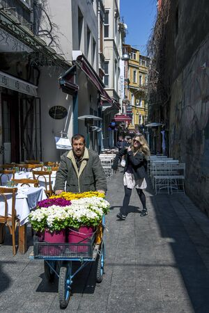 flower seller: A flower seller pushes his cart through an alley in the Taksim district of Istanbul in Turkey.