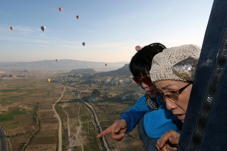 check out: Two Japanese passangers aboard a Voyager Balloon flight check out the scenery over the Goreme region of Cappadocia at sunrise.