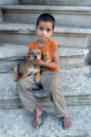 gitana: Un niño gitano que sostiene un perrito en Edirne, Turquía. Edirne tiene una de las mayores poblaciones de personas gitanas en Turquía.
