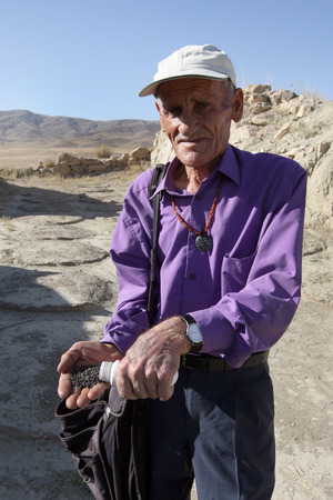 hundreds: A man with a hand full of grain believed to be hundreds of years old. He is standing infront of the ancient storage pits where the grain was collected from at the former Urartu kings Palace of Sarduri-Hinili. Located near Cavustepe in far eastern Turkey,  Editorial