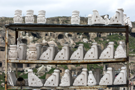 plaster cast: Plaster cast fairy chinmeys dry in the outside air before being painted at Urgup in the Cappadocia region of Turkey. Fairy chimneys are one of the main reasons tourists flock to Cappadocia, with many of these volcanic structures still showing the windows