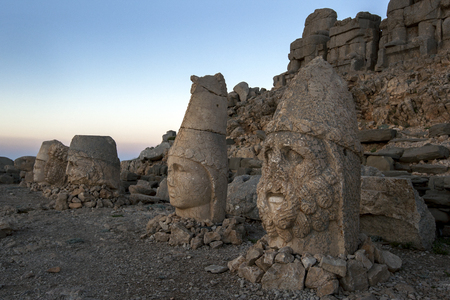 metres: Statues of goddess Tyche of Commagene far left, Zeus, Antichos and Hercules on the eastern platform at Mt Nemrut at sunrise. The Mt Nemrut National Park is situated in the Anti-Taurus mountain range 2150 metres in Turkey between Malatya to the north and K