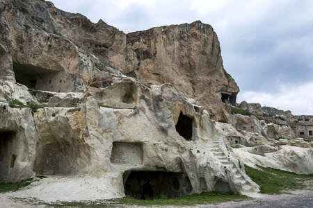 into: The ruins of ancient homes carved into a cliff face near Urgup in the Cappadocia region of Turkey.