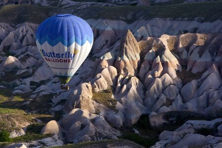 A hot air balloon navigates it way down the spectacular Rose Valley at sunrise, near Goreme in the Cappadocia region of Turkey.
