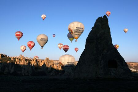 goreme: A group of hot air balloons soon after take off from near Goreme in the Cappadocia region of Turkey. Takeoff occurs as sunrise approaches when the wind conditions are most calm.