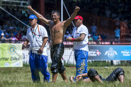 opponent: A wrestler celebrates victory at the Kirkpinar Turkish Oil Festival as his opponent lays dispondent on the turf. Edirne, Turkey. Editorial