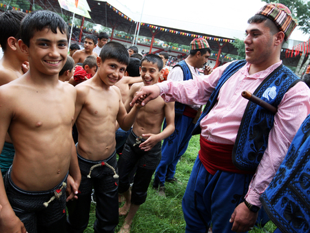 gitana: Young wrestlers greet a gypsy musician prior to the start of competition at the Kirkpinar Turkish Oil Wrestling Festival in Edirne, Turkey.