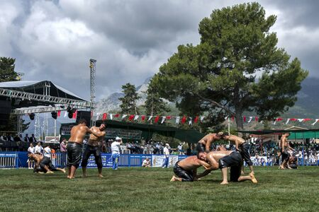 wrestlers: Wrestlers battle for victory at the Kemer Turkish Oil Wrestling Festival in Turkey as a storm approaches overhead.