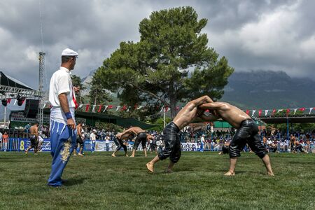 approaches: Wrestlers battle for victory at the Kemer Turkish Oil Wrestling Festival in Turkey as a storm approaches overhead.