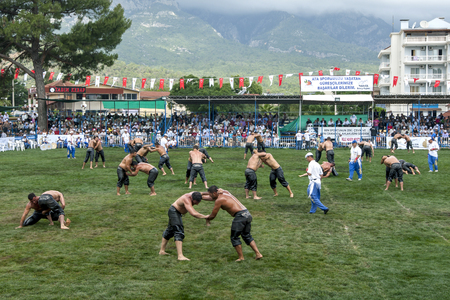wrestlers: A packed arena of wrestlers battle for victory at the Kemer Turkish Oil Wrestling Festival in Turkey as a storm approaches overhead. Editorial