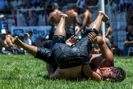 onto: A wrestler tosses his opponent onto his back during competition at theElmali Turkish Oil Wrestling Festival in Elmali in Turkey. Editorial