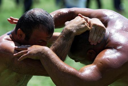 wrestlers: Wrestlers engaged in battle at the Kirkpinar Turkish Oil Wrestling Festival, Edirne, 2010. Editorial