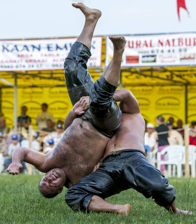 bout: A heavy weight wrestler is tossed onto the arena during the final bout at the Velimese Turkish Oil Wrestling Festival in Turkey.
