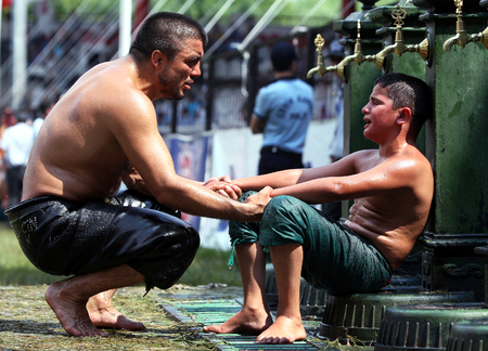 bout: A father comforts his son after he lost his bout at the Kirkpinar Turkish Oil Wrestling Festival, Edirne, 2009.