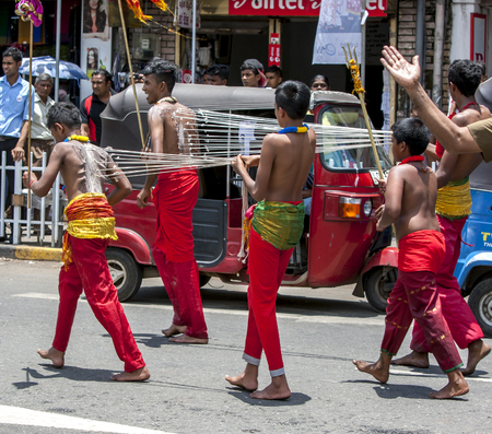 kavadi: Kavadi Dancers with hooks piercing their bodies moves through the streets of Kandy during the Day Perahera in Sri Lanka. The Kavadi Dancers are of Hindu faith but are still welcomed to perform during the Buddhist festival. The Esala Perahera Festival runs