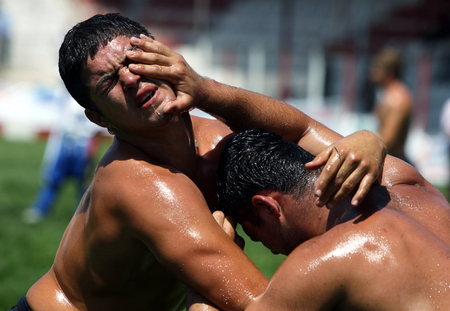 wrestlers: A wrestlers cops a finger to the eye during competition at the Kirkpinar Turkish Oil Wrestling Festival, Edirne, Turkey.