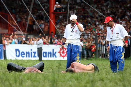 arbitros: Los árbitros inspeccionar un par de luchadores después de que ambos se derrumbó de agotamiento después de una feroz batalla en el Festival de Kirkpinar lucha en aceite turca en Edirne en Turquía.