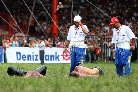arbitros: Referees inspect a pair of wrestlers after they both collapsed from exhaustion after a fierce battle at the Kirkpinar Turkish Oil Wrestling Festival in Edirne in Turkey.