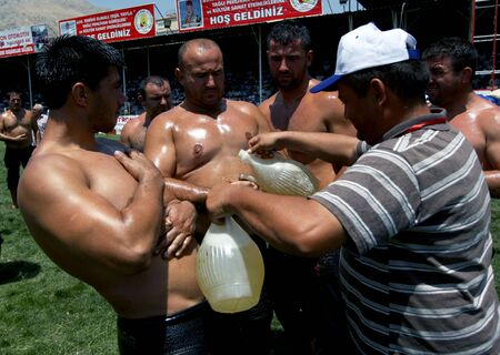 wrestlers: Wrestlers oil their bodies prior to competition at the Elmali Turkish Oil Wrestling Festival in Elmali, Turkey. Editorial