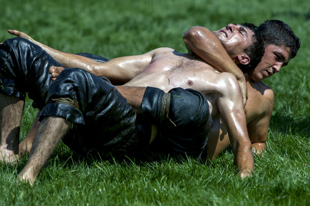 overpowered: A wrestler is overpowered by his opponent at the Elmali turkish Oil Wrestling Festival in Turkey.