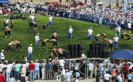 wrestlers: Wrestlers battle in front of a large crowd at the Izmit Turkish Oil Wrestling Festival in Turkey. Editorial