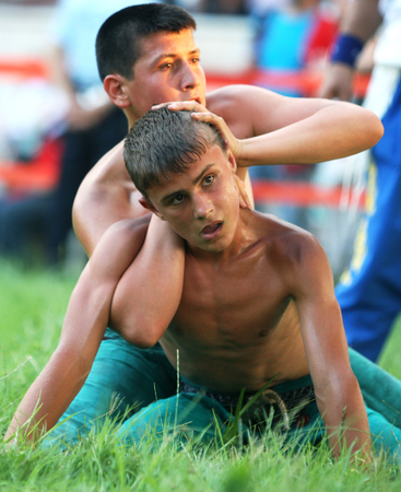 bout: A teenage wrestler takes control of his bout at the Kirkpinar Turkish Oil Wrestling Festival in Edirne in Turkey.