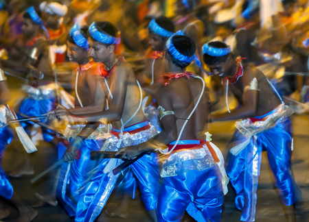 tapper: A group of Wood Tappers perform along the streets of Kandy during the Esala Perahera in Sri Lanka. The Esala Perahera festival runs every year in late July or early August for ten days, ending on the Nikini poya full moon and is held to honour the Sacred
