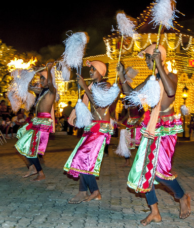 symbolically: Colourful Chamara Dancers performs a dance whereby the yak tail they hold symbolically fans the Sacred Tooth Relic during the Esala Perahara in Kandy, Sri Lanka. The Esala Perahera runs every year in late July or early August for ten days, ending on the N