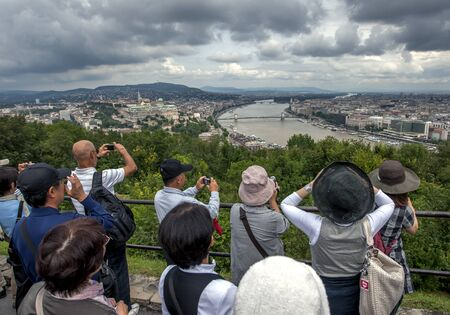 Tourists take photographs of the Danube River from the Citadel(Fortress) on Gellert Hill in Budapest in Hungary.
