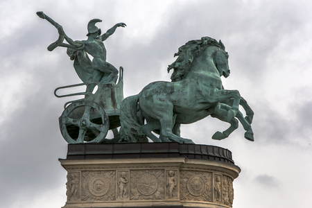heros: The statue of a man holding a snake driving his horse drawn chariot ( a symbol of war) in Heros Square in Budapest in Hungary. Construction of the Millennium Monument began in 1896 to commemorate the 1000th anniversary of the Hungarian conquest of the Ca Editorial