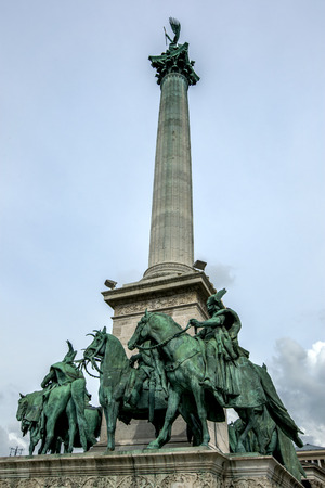 heros: The central column of the Millennium Monument showing several of the Seven Chieftains of the Magyars at its base. The monument is located in Heros Square in Budapest in Hungary. Construction of the Millennium Monument began in 1896 to commemorate the 100